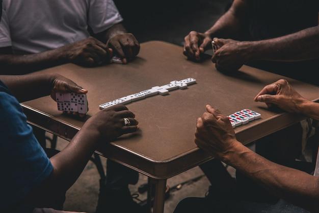 Nahaufnahmeaufnahme von vier afrikanischen leuten, die dominosteine um einen tisch spielen