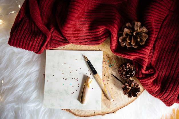 Nahaufnahmeaufnahme von weihnachtsbaumunebenheiten auf rotem stoff und einem stift mit glänzenden sternaufklebern