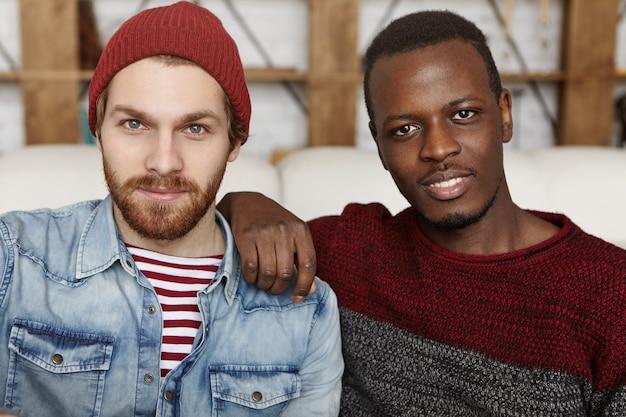 Nahaufnahmeaufnahme von zwei attraktiven stilvollen männlichen freunden verschiedener rassen, die sich im café entspannen
