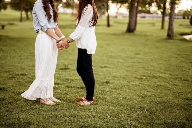 Nahaufnahmeaufnahme von zwei frauen, die hände halten, während sie in einem grasfeld mit unschärfe stehen