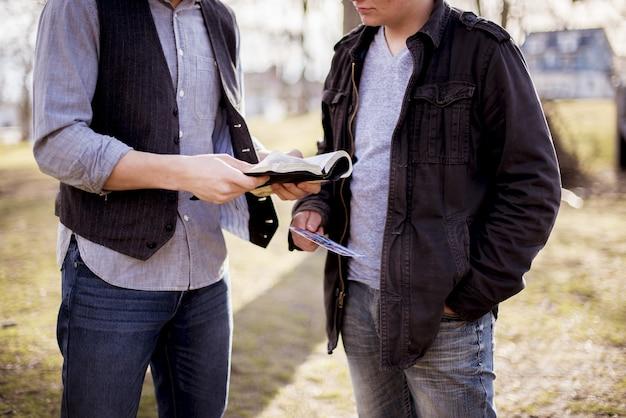Nahaufnahmeaufnahme von zwei männern, die nahe beieinander stehen und die bibel lesen
