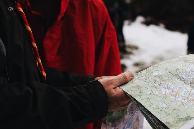 Nahaufnahmeaufnahme von zwei personen, die eine karte in einem schneebedeckten bereich halten und lesen