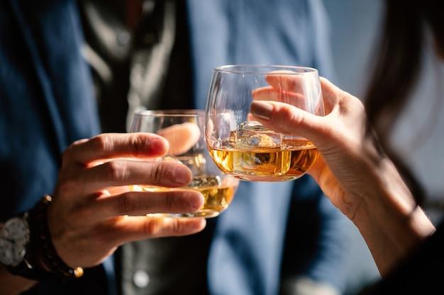 Nahaufnahmeaufnahme von zwei personen, die gläser mit alkohol an einem toast anstoßen