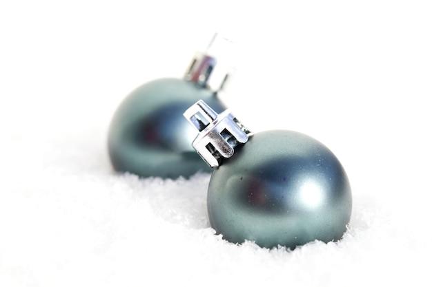 Nahaufnahmeaufnahme von zwei runden blauen weihnachtsverzierungen im schnee