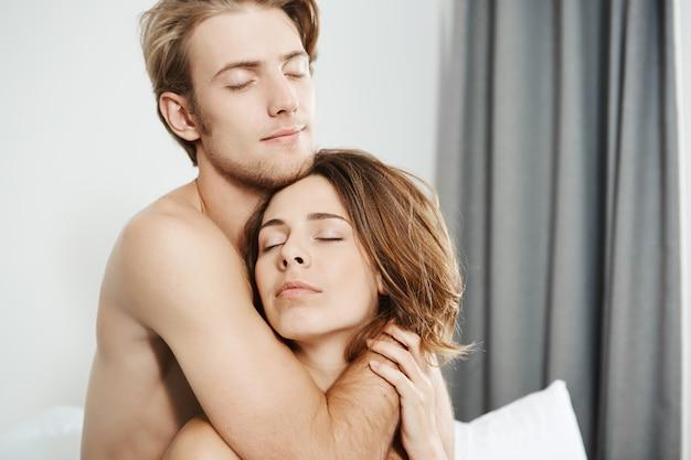 Nahaufnahmeaufnahme von zwei schönen zarten jungen erwachsenen in der liebe, die im bett mit geschlossenen augen und romantischem lächeln umarmen. paar auf hochzeitsreise genießen ersten morgen sie wachten zusammen auf