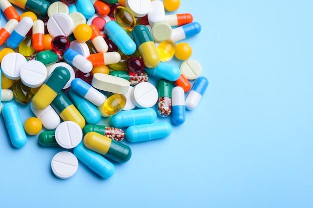 Nahaufnahmeaufnahme zahlreicher bunter kapseln und pillen auf blauem hintergrund