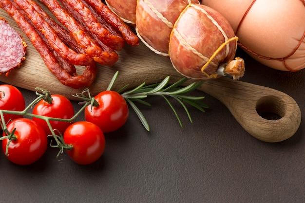 Nahaufnahmeauswahl des frischfleisches mit tomaten auf dem tisch