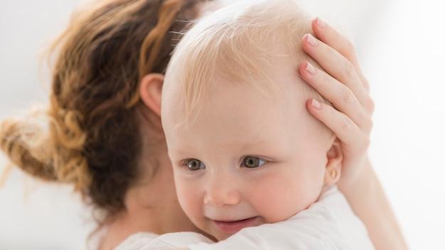 Nahaufnahmebaby, das glücklich ist, mit mutter zu sein
