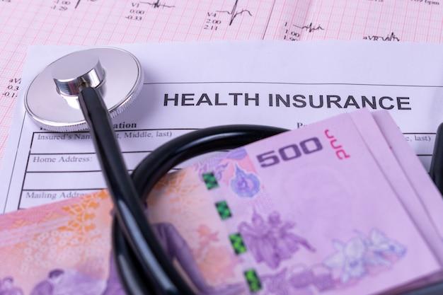 Nahaufnahmebanknote wurde stethoskop auf krankenversicherungsformular eingewickelt. krankenversicherung konzept.