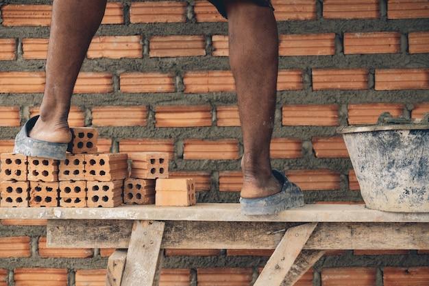 Nahaufnahmebein des berufsbauarbeiters ziegelsteine im neuen industriestandort legend
