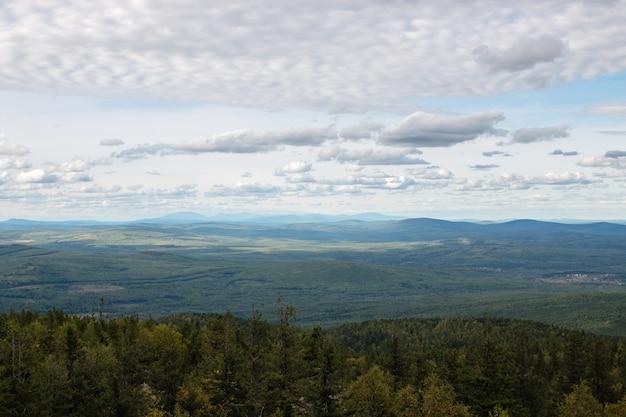 Nahaufnahmebergszenen im nationalpark kachkanar, russland, europa. bewölktes wetter, dramatischer blauer himmel, weit entfernte grüne bäume