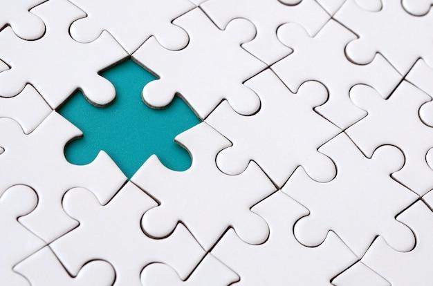Nahaufnahmebeschaffenheit eines weißen puzzlen in zusammengebautem zustand mit fehlenden elementen