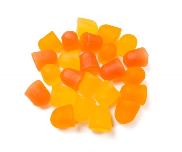 Nahaufnahmebeschaffenheit von orange und gelben multivitamingummis auf weißem hintergrund. gesundes lebensstilkonzept.