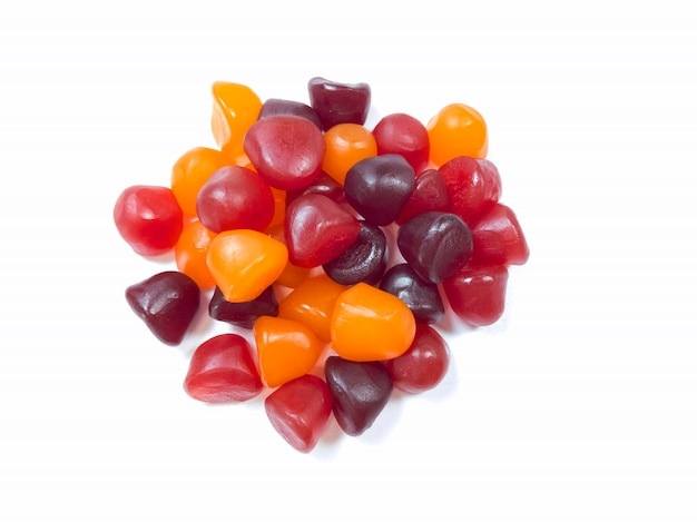 Nahaufnahmebeschaffenheit von roten, orange und lila multivitamingummis auf weißem hintergrund. gesundes lebensstilkonzept.