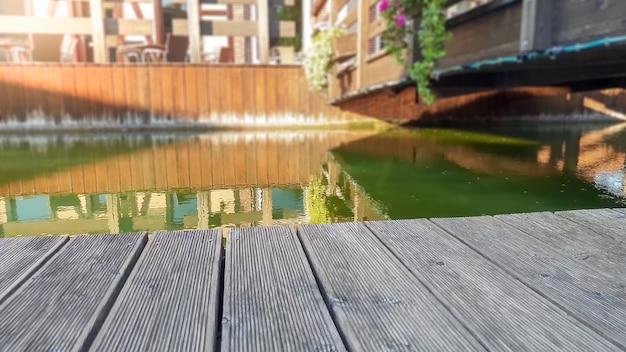 Nahaufnahmebild der alten hölzernen planke oder der bretter gegen ruhigen fluss und brücke in der alten europäischen stadt. platz kopieren. perfekter hintergrund zum einfügen ihres bildes, produkts oder objekts