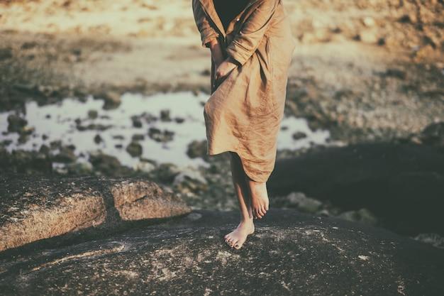Nahaufnahmebild der beine einer frau beim stehen auf dem felsen durch den strand