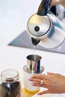 Nahaufnahmebild der frau, die heißes wasser auf gemahlenen kaffee im tropffilter gießt