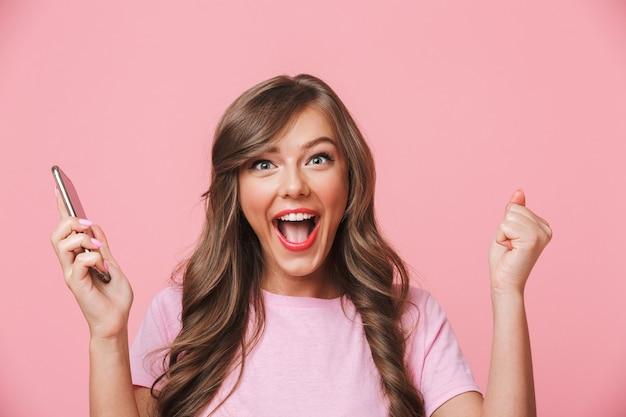 Nahaufnahmebild der fröhlichen positiven frau, die schöne lange haare schreien und geballte fäuste wie gewinner hat, lokalisiert über rosa hintergrund
