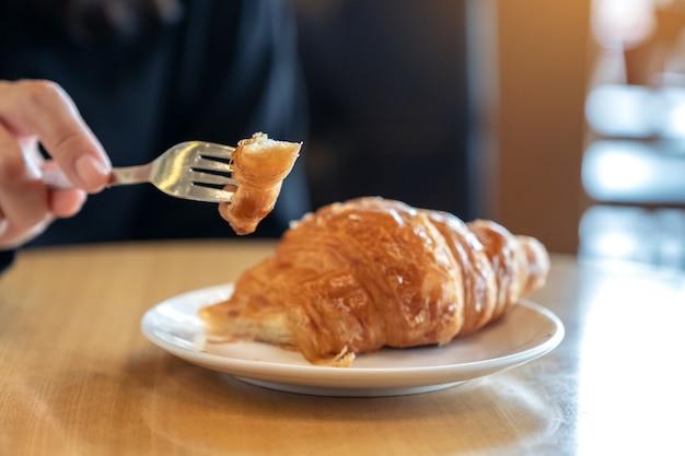 Nahaufnahmebild der hände, die ein stück croissant durch gabel zum frühstück auf holztisch schneiden