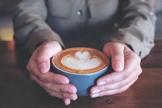 Nahaufnahmebild der hände, die eine blaue tasse heißen latte-kaffees mit latte-kunst auf holztisch im café halten