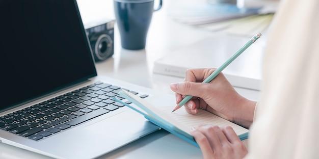 Nahaufnahmebild der hand der frau, die auf notizbuch mit bleistift schreibt, während sie an ihrem schreibtisch arbeitet.