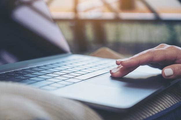 Nahaufnahmebild der hand einer frau, die laptop-touchpad verwendet und berührt