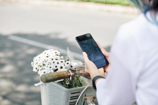 Nahaufnahmebild der jungen frau, die auf fahrrad sitzt und karte auf smartphone überprüft