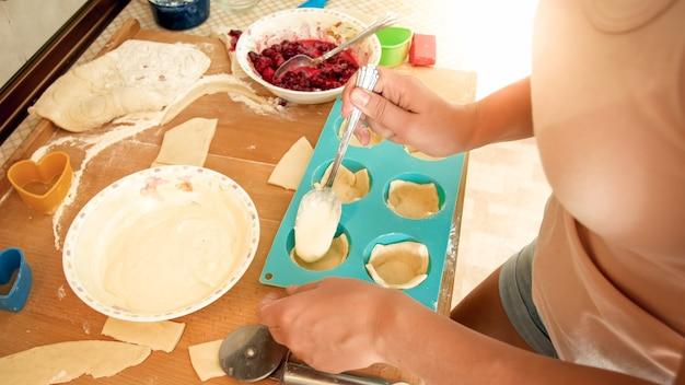 Nahaufnahmebild der jungen frau, die cupcakes macht