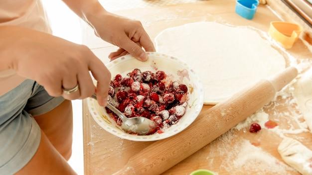 Nahaufnahmebild der jungen frau, die zucker mit beeren mischt. hausfrau macht beerensauce für süßen kuchen