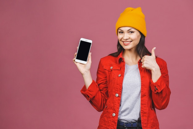 Nahaufnahmebild der jungen frau im lässigen präsentieren des copyspace-bildschirms des mobiltelefons und des daumen oben lokalisiert über rosa wand.