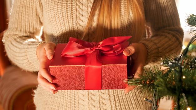 Nahaufnahmebild der jungen frau im pullover mit weihnachtsgeschenkbox mit rotem band