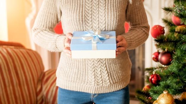 Nahaufnahmebild der jungen frau mit blauem kasten mit schleife gegen weihnachtsbaum im wohnzimmer