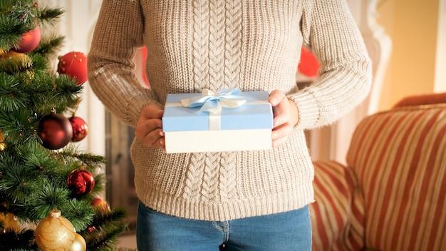 Nahaufnahmebild der jungen frau mit weihnachtsgeschenkbox, die auf wohnzimmer gegen schön verzierten weihnachtsbaum steht