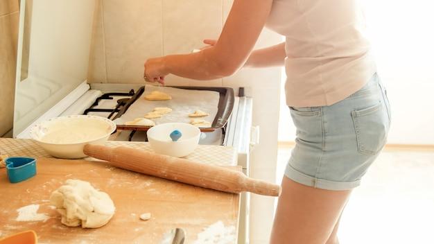 Nahaufnahmebild der jungen hausfrau, die geschnittene teigstücke auf backform setzt. frau backt kekse zu hause