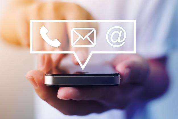 Nahaufnahmebild der männlichen hände unter verwendung des smartphones mit symbol telefon e-mail-handy und adresse. kontaktieren sie uns verbindungs- und e-mail-marketing-konzept