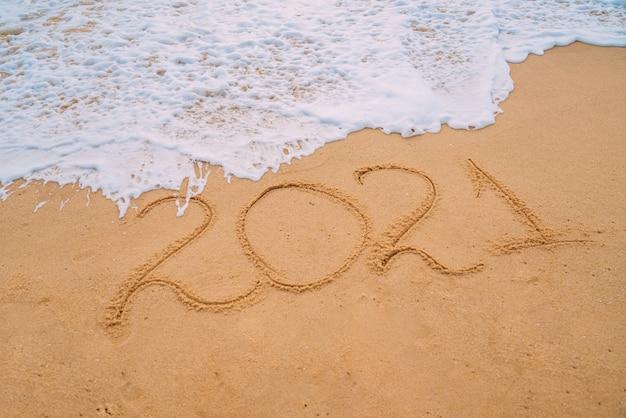 Nahaufnahmebild der meereswellen, die 2021 neujahrszahlen vom sand am strand waschen. konzept von neujahr, weihnachten und reisen in den winterferien