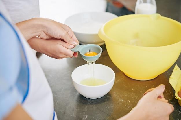 Nahaufnahmebild der mutter, die tochter zeigt, wie man kunststoffwerkzeug zum trennen von eiweiß und eigelb verwendet