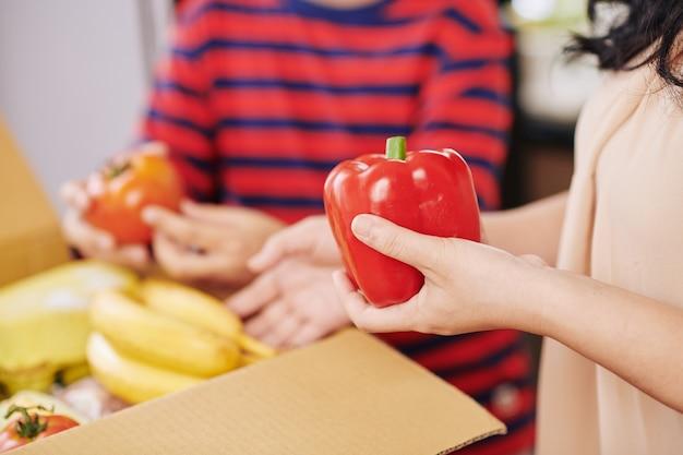 Nahaufnahmebild der reifen hausfrau, die gemüse aus dem karton nimmt, den sie online bestellte