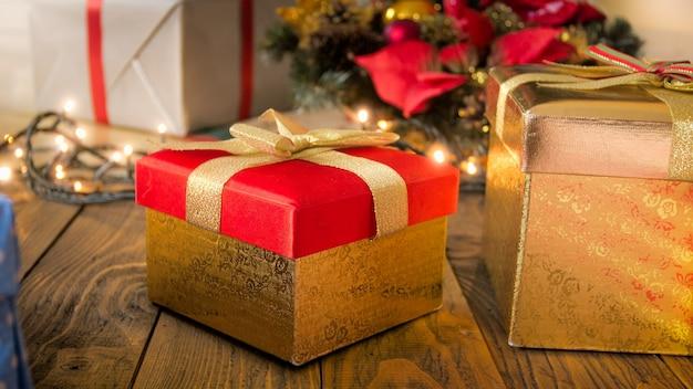 Nahaufnahmebild der roten weihnachtsgeschenkbox mit goldenem band und leuchtenden lichtern