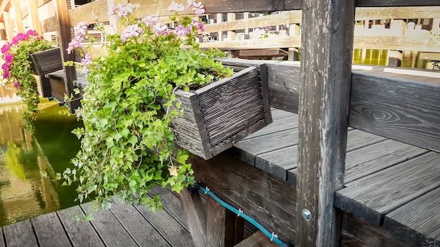 Nahaufnahmebild der schönen alten holzbrücke mit blumen, die in töpfen über ruhigem fluss in der europäischen stadt wachsen