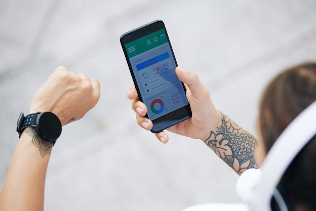 Nahaufnahmebild der sportlerin, die gesundheitsanwendung auf smartphone prüft, wenn sie mit smartwatch synchronisiert