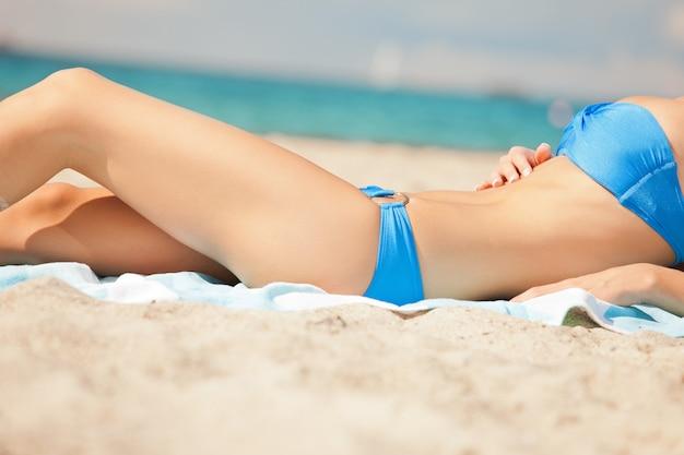 Nahaufnahmebild der weiblichen beine und des bikinis.