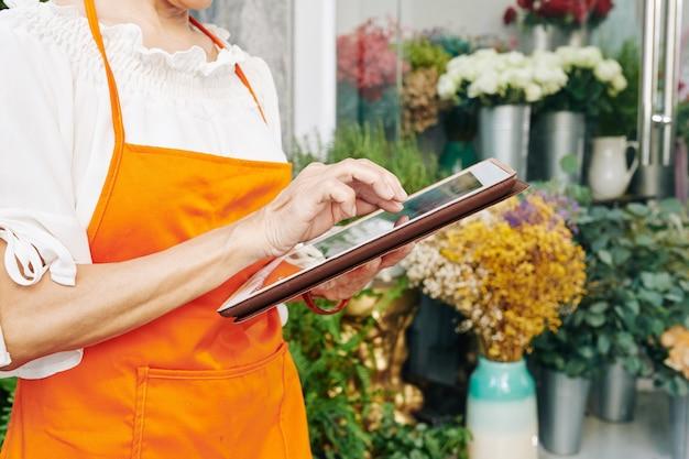 Nahaufnahmebild des älteren floristen, der anwendung auf tablet-computer verwendet, um online-bestellungen von kunden anzunehmen
