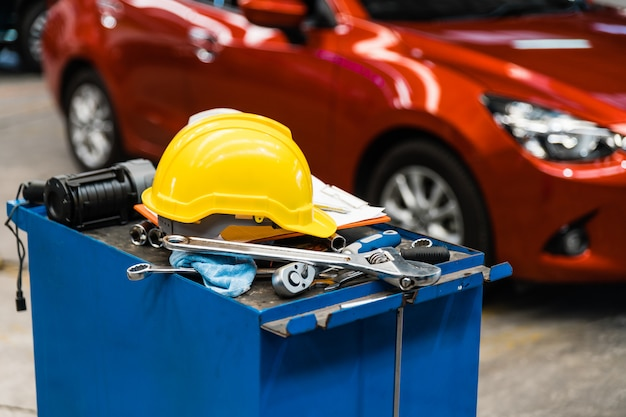 Nahaufnahmebild des blauen metallwerkzeugschranks mit schutzhelmen, handschuh, dokumentenblock auf dem schrank mit garage. autoreparaturservice.