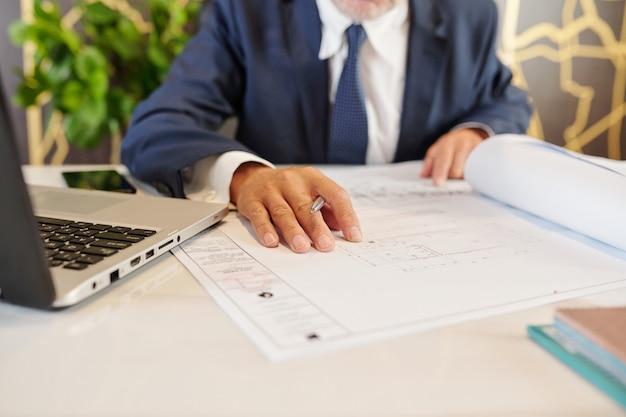 Nahaufnahmebild des firmeninhabers, der blaupause des neuen bürogebäudes prüft, das er kaufen wird