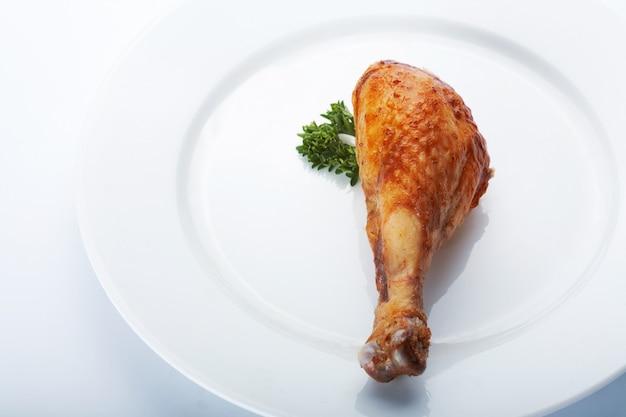 Nahaufnahmebild des gebratenen hühnerbeins auf der weißen platte.
