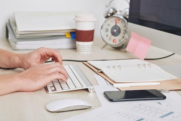 Nahaufnahmebild des geschäftsmannes, der am computer an seinem schreibtisch mit geöffnetem planer, smartphone und stapel von dicuments arbeitet