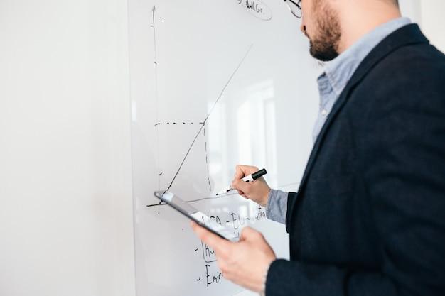 Nahaufnahmebild des jungen dunkelhaarigen mannes in den gläsern, die einen geschäftsplan auf whiteboard schreiben. blick von der seite, fokus auf der hand.