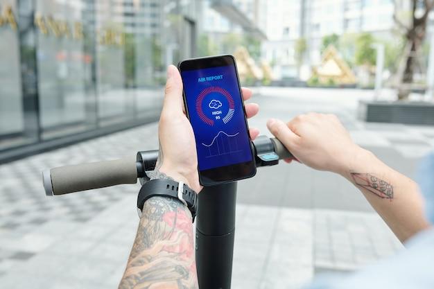 Nahaufnahmebild des mannes, der luftbericht über mobile anwendung prüft, wenn auf roller zur arbeit gefahren wird