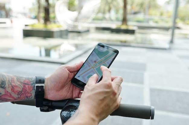 Nahaufnahmebild des mannes, der navigationskarte auf smartphone überprüft, bevor er auf roller fährt